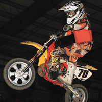 A young boy on a mini bike flying through the air.