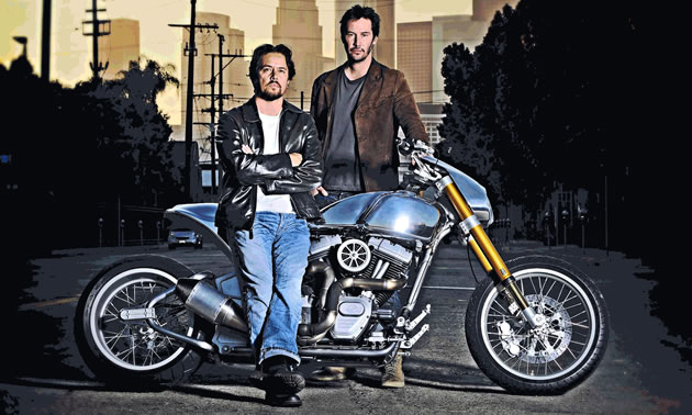Gard Hollinger and Keanu Reeves pose in front of and behind a KRGT-1 motorcycle.