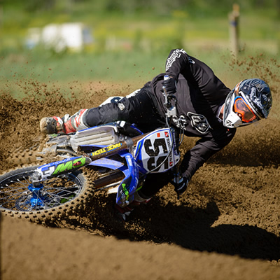 Professional motocross racer Keylan Meston leans hard into a corner on a dirt track.