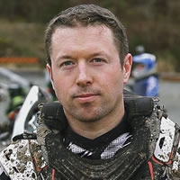 A brown haired man in dirt bike riding gear.