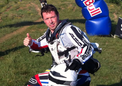 A brown haired man putting the thumbs up while sitting on his bike in front of Red Bull sign.
