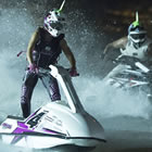 Photo of two people standing on jet skis and racing them in the dark.