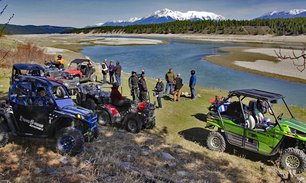 A group of ATVs and side-by-sides parked beside the Kootenay River.
