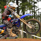 Photo of a guy riding a blue dirt bike.