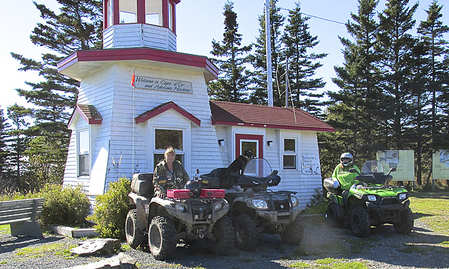 Three ATVs parked at a lighthouse in Nova Scotia.