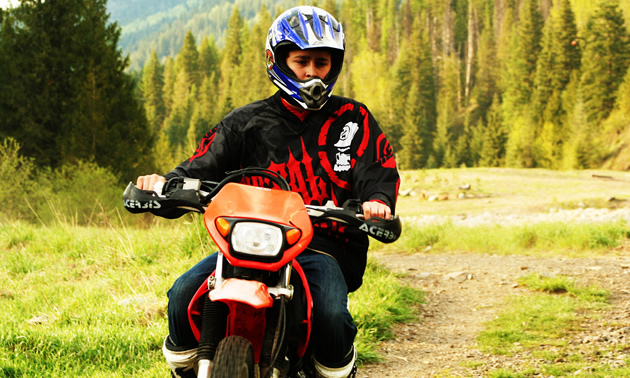 A boy in a blue helmet riding wearing a black and red long sleeve shirt riding a orange dirt bike on a grassy trail in the backcountry.