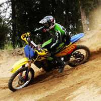A guy in motocross gear ripping it up on the sand.
