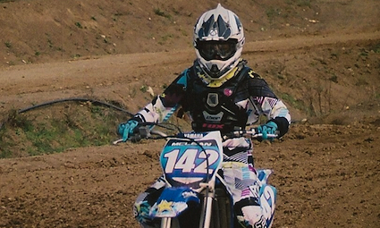 A young lady riding a dirt bike