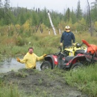 Man in mud waist deep next to a man standing by an ATV