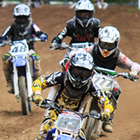 Photo of a group of young kids riding their dirt bikes down a dirt track towards the camera.
