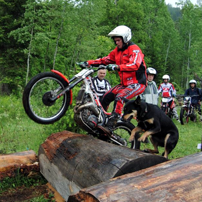 Sam King wheelieing over some logs.