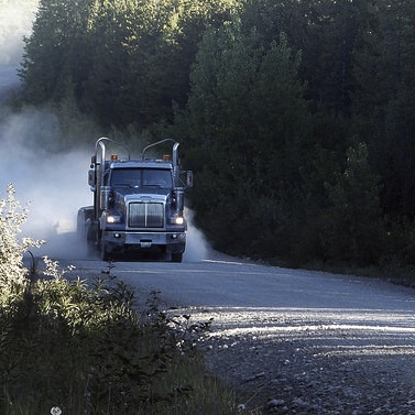 A logging truck coming down a logging road.  There are trees on both sides of the road and dust billowing behind the truck.