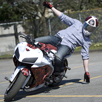 A guy hanging off the side of a streetbike.