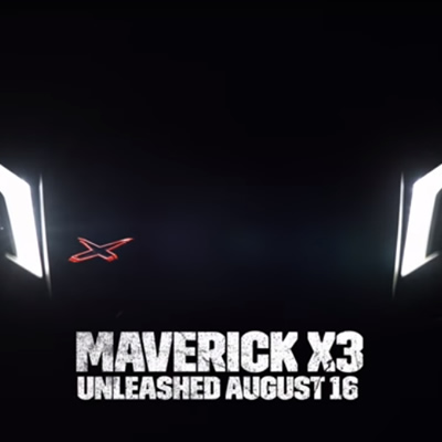 Screen capture of Maverick X3 trailer, showing headlights against black blackground, with words 'Maverick X3 - Unleashed August 16th'