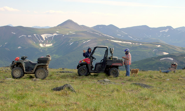 A RZR and a quad parked on a mountain meadow.