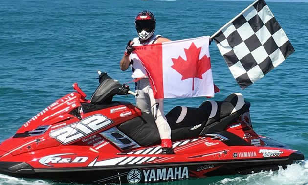 Mike Klippenstein on a PWC holding a Canadian flag and the finish line flag.