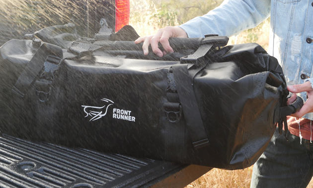 Monsoon Bag being put in the back of a pickup truck.