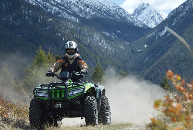 A man on a green ATV with the mountains in the background.