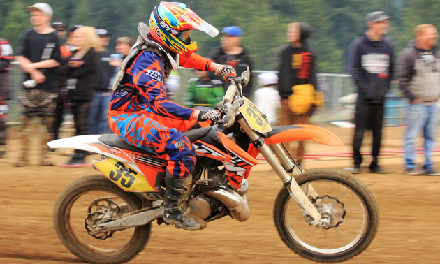 Photo of a guy riding an orange dirt bike with spectators watching him.