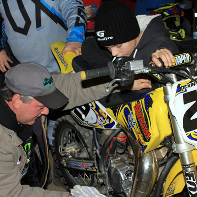 A motocross father fixing his son's dirt bike.