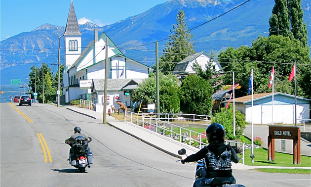 Two motorcyclists riding through Kaslo.