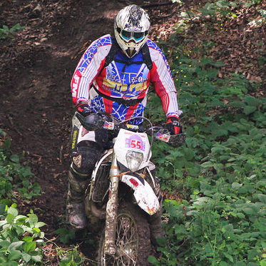 An off-road rider is going down a dirt trail through some bushes.