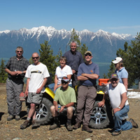 A group of people sitting together around a quad at the top of a mountain.