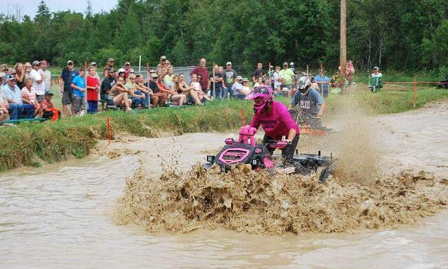 Anne Kotula of Grand Rapis Minnesota riding her ATV through a mud bog.