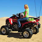 A woman on a quad in the desert.