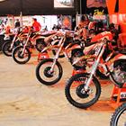 Half a dozen orange dirt bikes parked in a line beside a trailer under an orange tent.