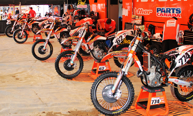 Half a dozen orange dirt bikes parked in a line beside a trailer under an orange tent.