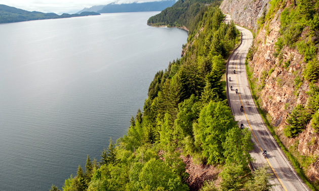 Motorcycles riding along twisty Kootenay Lake road.