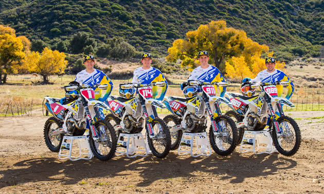 Four dirt bike riders lined up beside their bikes.