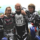 Three people wearing riding gear and smiling