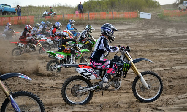 A group of motocrossers taking off from the starting gate.