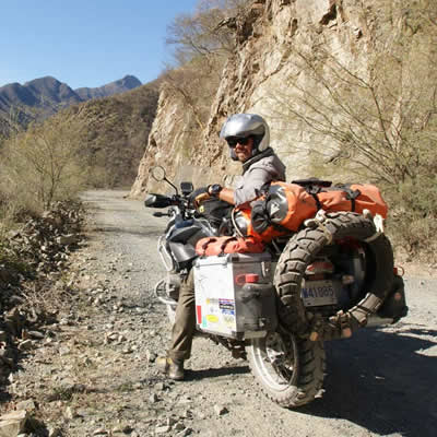 Kevin Chow on his BMW adventure bike, riding down a dirt road through canyons.