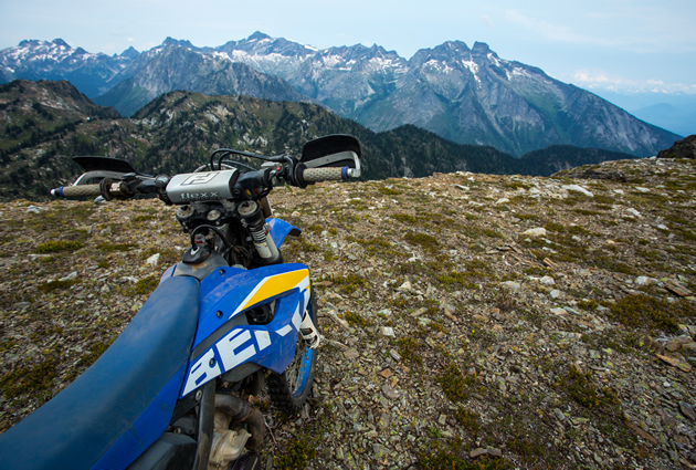 A dirt bike parked on top of a mountain.