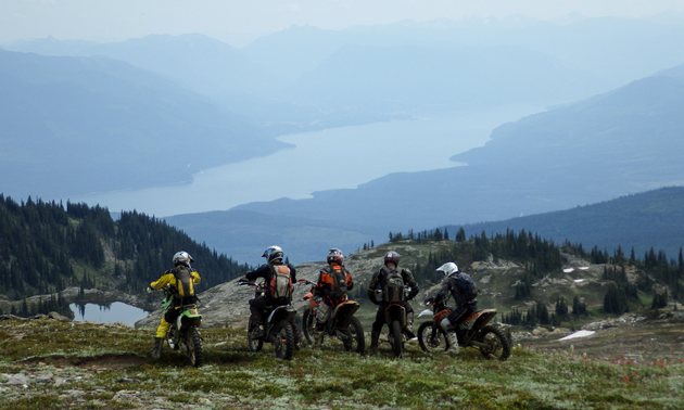 A group of dirt bikers enjoying a view of a lake.