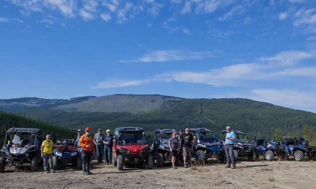 A group of ATV and side-by-side riders on top of a mountain.