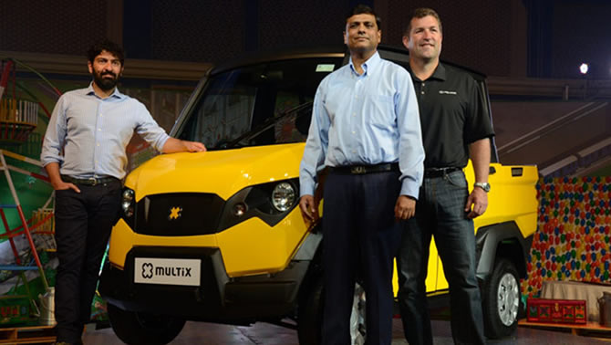 Picture showing 3 men standing in front of the Multix, a yellow and black personal utility vehicle.