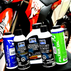 Products for oiling and cleaning air filters lined up with a bike in the background.