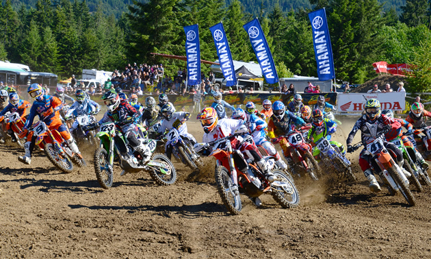 A group of motocross racers coming off the starting line.