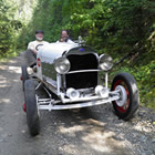 Photo of two older gentlemen sitting behind the wheel of a classic speedster car on a trail in the bush.