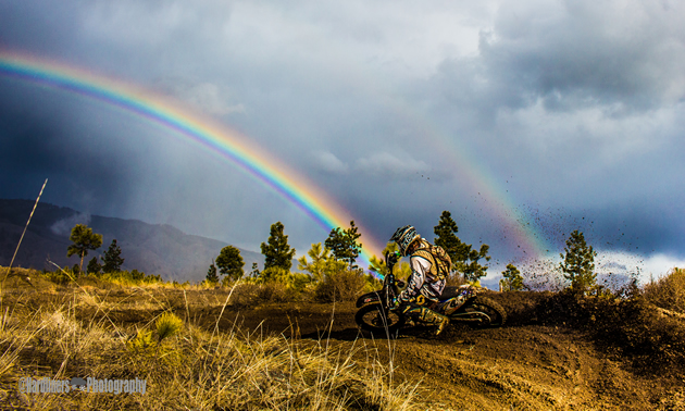 A dirt bike rider hits a berm right with a rainbow in the background.