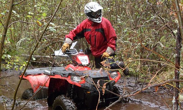 Lady riding a quad in the rain in Chitek Lake, Saskatchewan