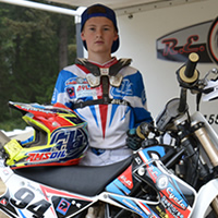 A young boy dressed in full moto gear standing by a race dirt bike.