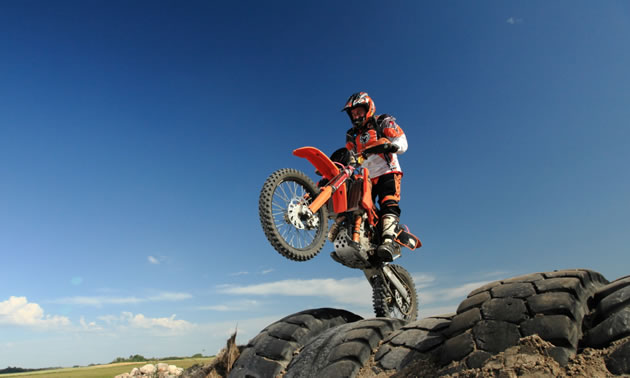 A rider on an orange KTM tackling a tire section on an endurocross track.