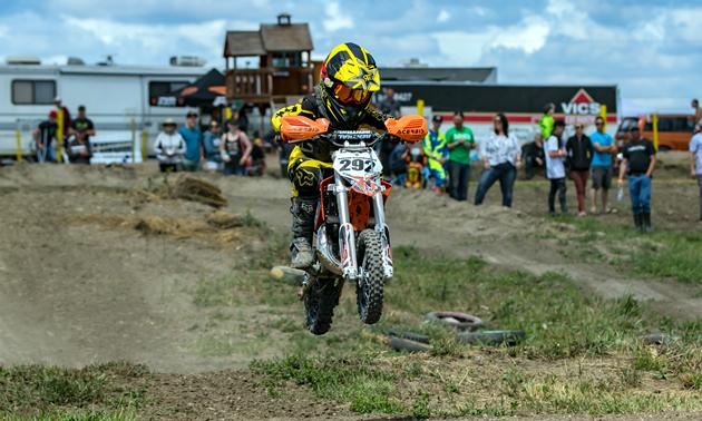 A little kid jumping a motocross dirt bike.