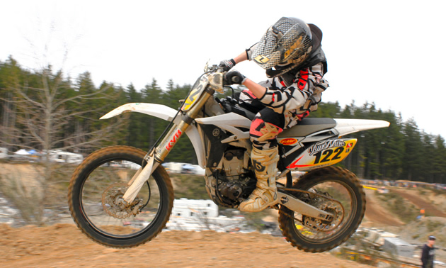 Photo of a guy in the air riding a white dirt bike.