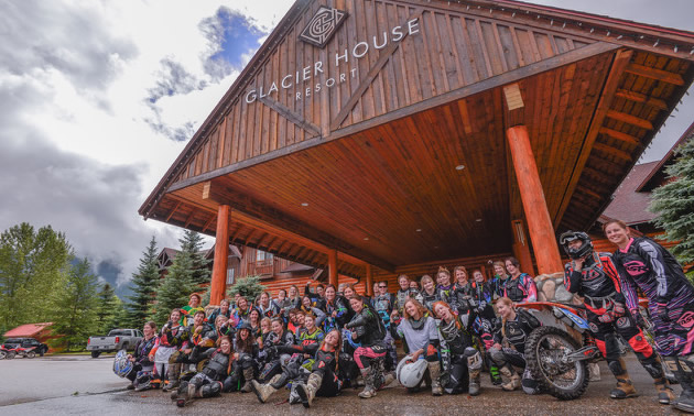 A group of women dirt bike riders gathered in front of Glacier House Resort.